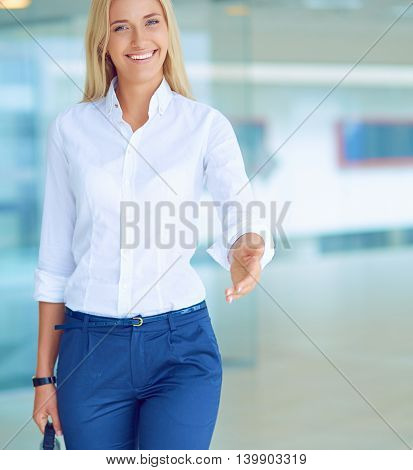 Young business woman ready to handshake standing in office.