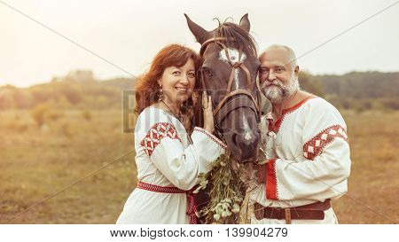 Mature Man And Woman In Ethnic Clothes Are Posing With The Horse On The Rural Summer Background.