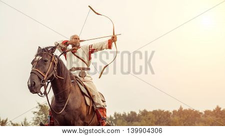 Man In Ethnic Clothing Is Riding A Horse And Aiming From The Bow.