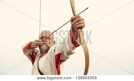 Man In Ethnic Clothing Is Aiming From The Bow On The Clear Sky Background.