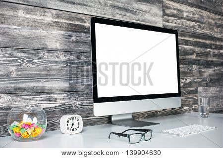 Closeup and side view of creative workspace with blank white computer monitor keyboard glass of water specs clock and decorative glass bowl on wooden plank wall background. Mock up