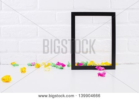 Empty see-through picture frame and colorful crumpled paper pieces on white brick background. Mock up