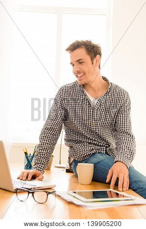 Portrait Of Smiling Man Sitting On Table And Using Laptop