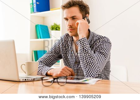 Portrait Of Serious Young Businessman Talking On Mobile Phone