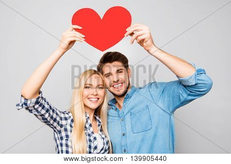 Young Smiling Family Holding Paper Heart Under Head