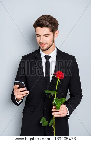 Happy Man With Rose Waiting For His Girlfriend And Reading Sms