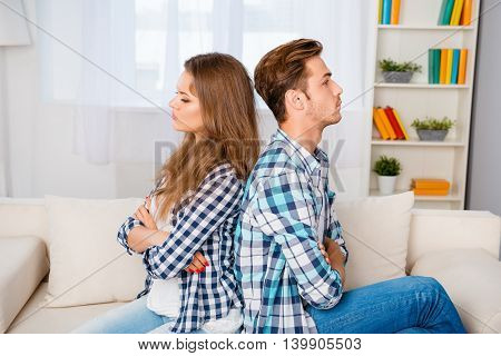 Young Angry Couple With Crossed Hands Sitting On Sofa Back To Back