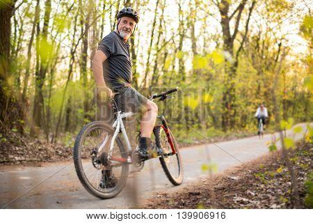 Senior man on his mountain bike outdoors (shallow DOF; color toned image)