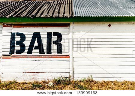 Abandoned front of a bar built with white woods with a lake behind