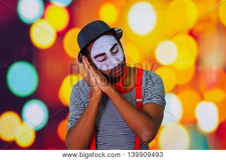 Headshot pantomime man with facial paint posing for camera using hands interacting sleeping, blurry lights background.
