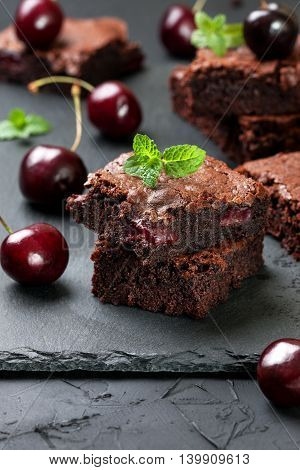 few pieces of brownie with cherries and mint on a black concrete background
