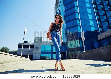 Slim attractive young woman in casual clothes and sunglasses on business center background photographed from low camera angle