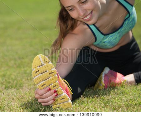 Smiling teenage runner stretching to grab her soles.