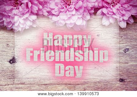 pink flowers on wooden with word Happy Friendship Day