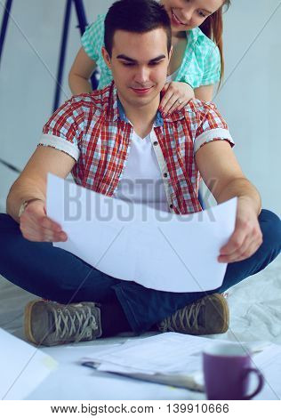 Young couple sitting on floor and calculating about they savings