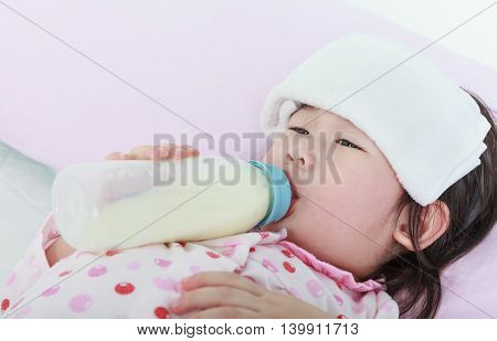 Closeup sick asian girl sucking up milk bottle and lying in bed. Drinking milk for good health.