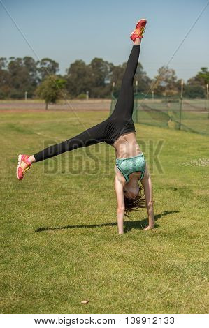 Female athlete in black tights finishing a cartwheel.