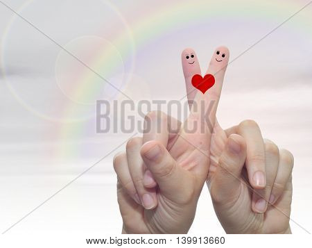 Concept or conceptual human or female hands with two fingers painted with a red heart and smiley faces over rainbow sky background