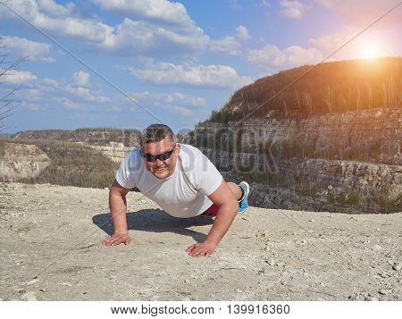 Man Doing Pushups Outdoors In Nature.