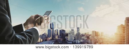 Businessman using mobile phone with panoramic cityscape of Bangkok city in sunrise, vintage tone