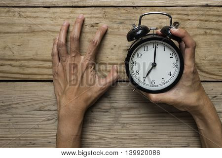 Stressed woman with clock in her hand on the table