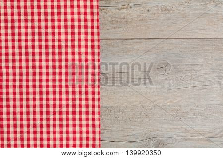 Wooden table covered with red checked tablecloth. View from the top.