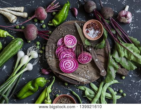 Chopped beets peppers onions green beans spices on a dark background. Fresh garden vegetables. Vegetarian detox diet food