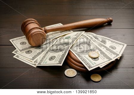 Gavel with dollars and cents on a brown lacquered wooden table close up. Concept of corruption and bribery