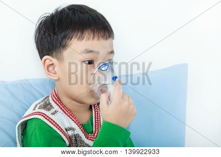 Sad asian child holds a mask vapor inhaler for treatment of asthma on sickbed in hospital. Breathing through a steam nebulizer. Concept of inhalation therapy apparatus.