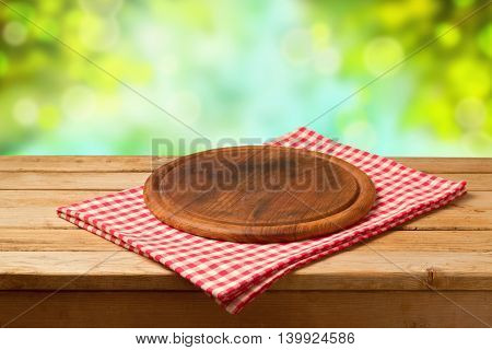 Round board on tablecloth on wooden table over bokeh background. Ready for product montage display