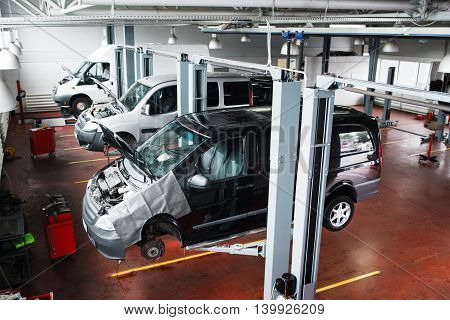 Industrial car lifting at modern repair shop. Minibuses service maintenance at professional workshop.