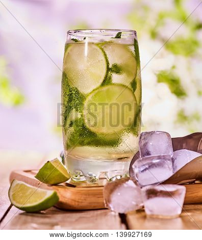 Alcohol cocktail. Wooden boards is glass with alcohol drink and ice cubes. Drink number two hundred fifty nine cocktail mohito and scoop ice . Country life cocktail . Summer outdoor. Light background.