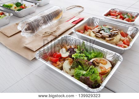 Healthy food and diet concept. Take away of fitness meal. Weight loss nutrition in foil boxes. Vegetables, lettuce and mozarella cheese with shrimps, paper bag and water bottle at white wood