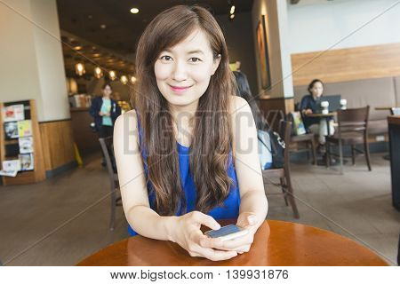 Woman look at cellphone in coffee shop