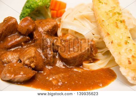 Pork stew with pasta on a white background