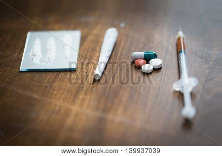 drug use, crime, addiction and substance abuse concept - close up of crack cocaine drug dose track on mirror with marijuana joint, pills and syringe