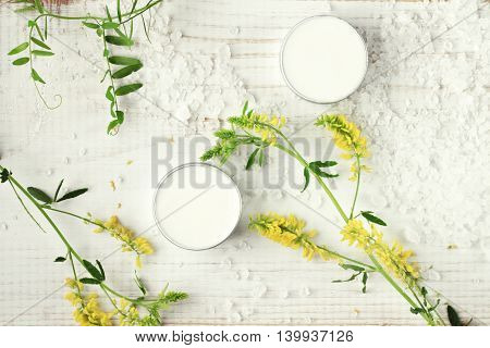 Body care cream in sample jars, sea salt, green herb. Top view, white spa set background.