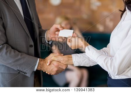 Mid-section of business colleagues exchanging business card at restaurant