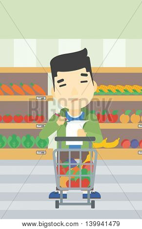 An asian thoughtful man standing at the supermarket with supermarket trolley full with products and holding a shopping list in hands. Vector flat design illustration. Vertical layout.