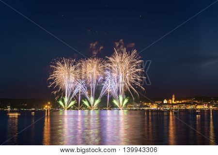 Fireworks on the lakefront of Arona in a summer party night seen from Angera Major Lake- Piedmont