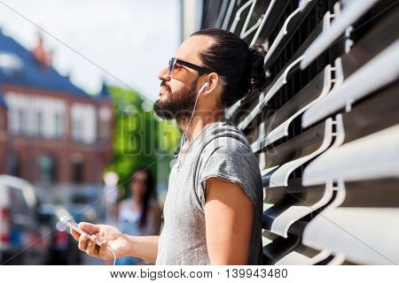 people, music, technology, leisure and lifestyle - happy young hipster man with earphones and smartphone on city street