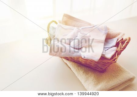 clothing, babyhood, motherhood and object concept - close up of white baby bootees with pile of clothes and towel for newborn boy in basket on table poster