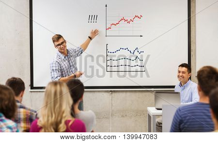 education, high school, learning, technology and people concept - student standing with remote control in front of teacher and classmates and showing chart on white board in classroom
