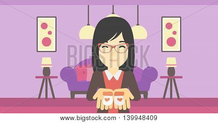 An asian pregnant woman holding baby booties in hands on the background of living room. Vector flat design illustration. Horizontal layout.