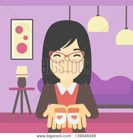 An asian pregnant woman holding baby booties in hands on the background of living room. Vector flat design illustration. Square layout.