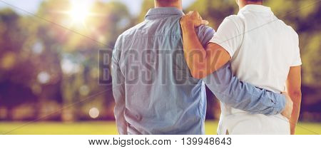 people, homosexuality, same-sex marriage, gay and love concept - close up of happy male gay couple or friends hugging from back over natural outdoor background