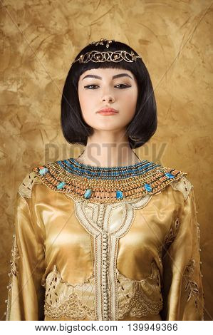 Photo of serious woman with Cleopatra makeup, closeup portrait of beautiful female with stylish haircut agaist golden background, young lady wearing fashionable golden necklace, beauty salon