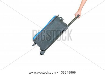 Closeup woman hand dragging blue luggage isolated on white background fabric luggage with plastic roller for travel concept