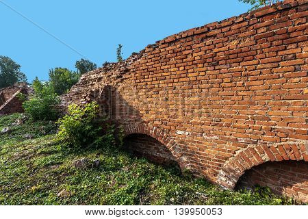 Half-ruined medieval monastic wall with traces of unsuccessful restoration.