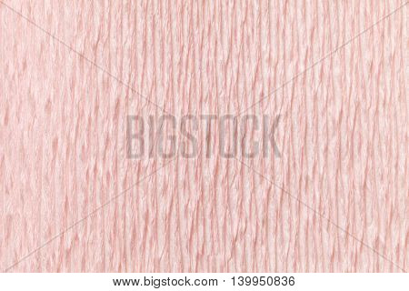 Textural light pink background of wavy corrugated paper close-up. Structural crepe cardboard macro shooting.
